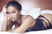 Sensual sexy african woman liyng on the bed in black lingerie — Stock Photo