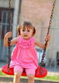 Happy little girl on a swing — Stock Photo