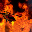 Helicopter flying by a bushfire — Stock Photo