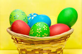 Colored eggs in basket — Stock Photo