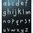 Complete english alphabet handwritten with white chalk on a blac — Stock Photo #10212362