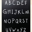 Complete english alphabet handwritten with white chalk on a blac — Stock Photo