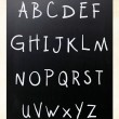 Complete english alphabet handwritten with white chalk on a blac — Stock Photo #10212598