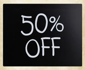 « 50 % de réduction » écrit à la main avec la craie blanche sur un tableau noir — Photo