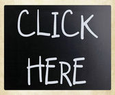 """Click here"" handwritten with white chalk on a blackboard — Stock Photo"