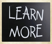 """Learn More"" handwritten with white chalk on a blackboard — Stock Photo"