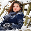 Young woman sitting in the snow — Stok fotoğraf