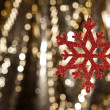 Red snow flake on a gold glitter background — Stock Photo #10415335