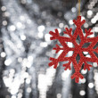 Royalty-Free Stock Photo: Red snow flake on a silver glitter background