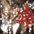 Stock Photo: Red snow flake on a gold glitter background