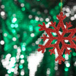 Red snow flake on a green, silver glitter background — Stock Photo