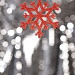 Red snow flake on a silver glitter background — Stock Photo