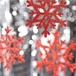 Red snow flake on a silver glitter background — Stock Photo #10415473