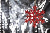 Floco de neve de vermelho sobre um fundo de glitter prata — Foto Stock