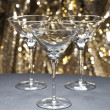Three Martini glasses in front of glitter background - Stock Photo