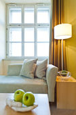Window illuminates a seating area with fruit in the foreground — Stock Photo