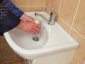 A person washing their hands in the bathroom sink . — Stock Photo
