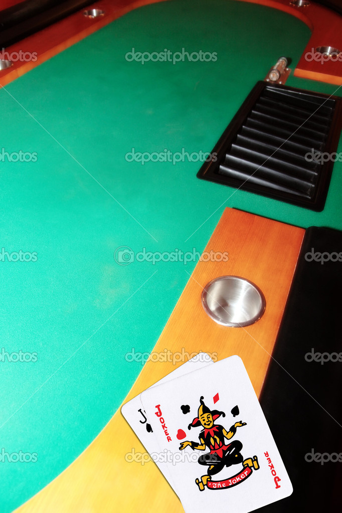 Green casino table with copy space and the jack of spades and joker representing a blackjack game  Stock Photo #10647644