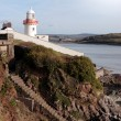 Stock Photo: Lighthouse with steps down to rocky beach during sunny day
