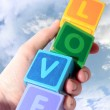 Love in wooden play block letters held in hand against clouds — Stock Photo #8089152