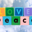 Royalty-Free Stock Photo: Love on peace in wood play block letters against clouds