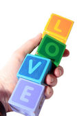 Love in wooden play block letters held in hand — Stock Photo