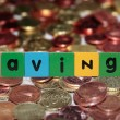 Coin savings in toy letters - ストック写真