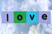 Love against clouds with clipping path — Stockfoto
