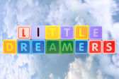 Little dreamers on toy blocks in clouds — Stock Photo