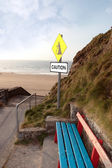 Bench and beach landslide caution sign — Stock Photo