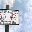 Scoop the poop sign against clouds - Stock Photo