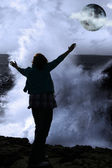 One woman with raised hands facing a wave and full moon on cliff — Stock Photo