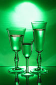 Three wineglasses on the mirror in the green light — 图库照片