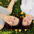 Two beautiful young girls lie side by side on the grass — Stock Photo