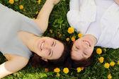 две красивые молодые девушки лежат бок о бок на траве — Стоковое фото