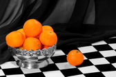 Some tangerines in the metal bowl on the chess board — Stock Photo