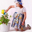 A little girl waters plants — Stock Photo