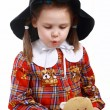 A little girl in the hat plays with a teddy bear — Stock Photo