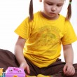 A little girl plays with toy cars and houses — Stock Photo