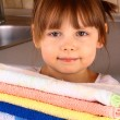 A little girl holds towels after washing — Stock Photo