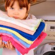 Stock Photo: Little girl is going to wash towels in washing machine
