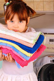 A little girl is going to wash the towels in the washing machine — Stock Photo