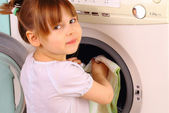 A little girl puts the towels in the washing machine — Stock Photo