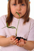 Little girl holds a plant in her hands with care — Stock Photo