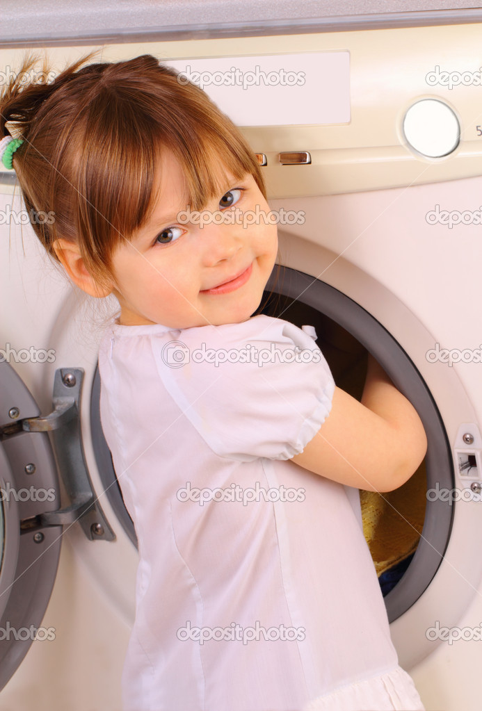 Funny little girl puts the towels in the washing machine with care — Stock Photo #9334828