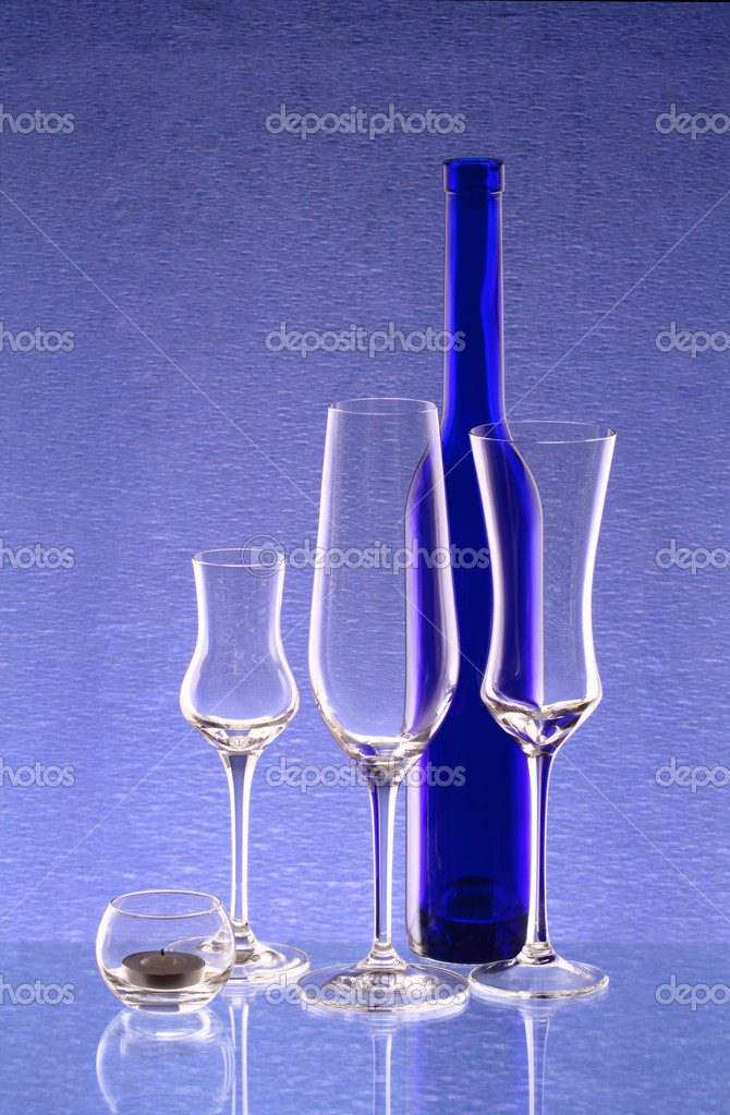 Blue bottle, three wineglasses and a candlestick on the mirror — Stock Photo #9467071