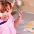 Stock Photo: Happy little girl cooks biscuits in the kitchen