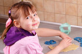 Funny little girl prepares a cake in the kitchen — Stock Photo