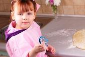 Lilla flickan förbereder en tårta i köket — Stockfoto