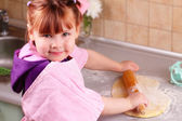 Little girl rolls the dough — Stock Photo